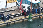 Body encased in metal drum is retrieved from the sea by police