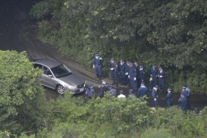 Japanese police search the mountain area where the victim's body was found.