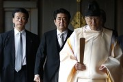 Japan's Prime Minister Shinzo Abe (C) is led by a Shinto priest as he visits Yasukuni shrine in Tokyo December 26, 2013. Abe visited Tokyo's Yasukuni Shrine for war dead on Thursday, in a move likely to anger Asian neighbour China and South Korea. REUTERS/Toru Hanai