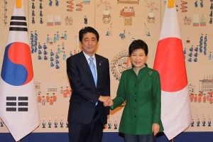 Park Geun-hye and Abe Shinzo shake hands following comfort women agreement.